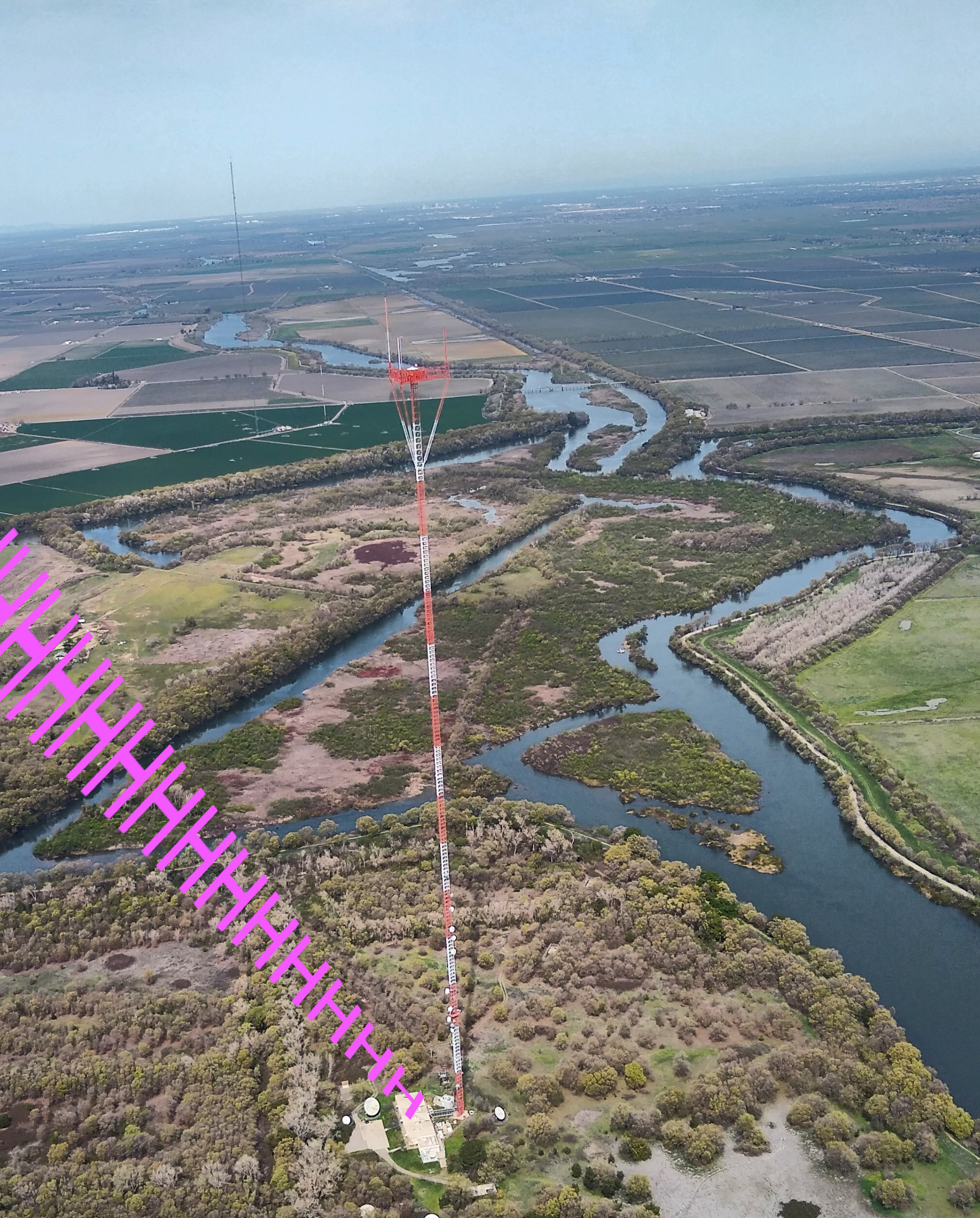 """Aerial view of a broadcast tower with """"HHHHHHH"""" emanating from the transmitter building."""